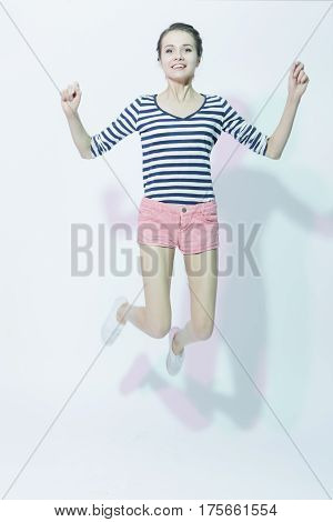 Portrait of Exclaiming Happy Caucasian Girl in Shorts Jumping Against White Background. Vertical Image