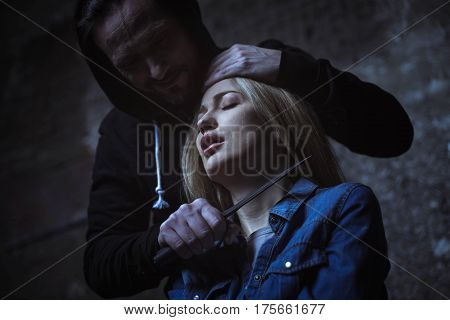 No one can stop me. Crazy wicked monstrous offender holding a dagger at womans neck and questioning her for secret information while keeping her hostage