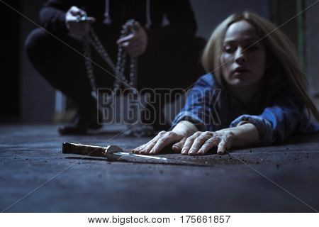 Almost saved myself. Captured young blonde girl trying reaching a knife which is lying near her while her kidnapper getting ready to tie her up