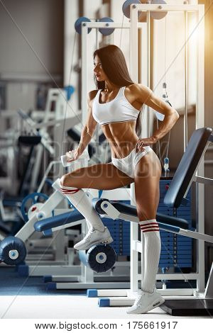 Muscular and strong woman seductive posing, holding hand on waist and turned away. Athletic brunette girl wearing in white sport wear training in gym and posing on professional sport equipment.