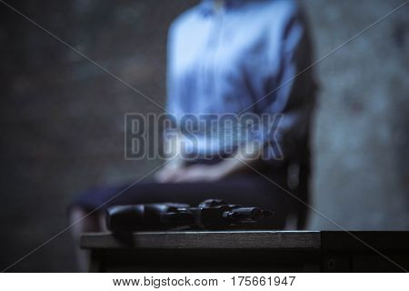 Not following business rules. Young neat scared lady sitting on a chair with her hands being roped while a gun lying tight near her