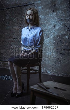 I wish I wasnt here. Anxious helpless bank worker sitting in a dark room being tied up to a chair while looking at the dagger lying nearby