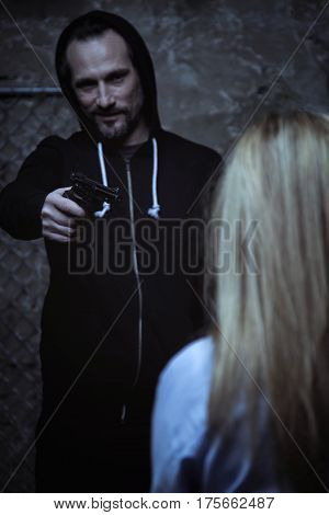 You have to obey my will. Lawless brutal crazy criminal pointing his weapon toward victim while standing in a dark room and wearing all black