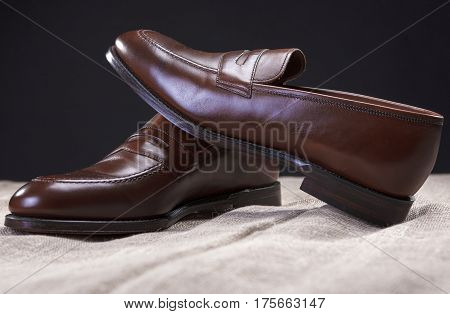 Footwear Concepts and Ideas. Pair of Brown Stylish Leather Penny Loafer Shoes Placed On Mesh Surface Against Black Background.Horizontal Image Orientation