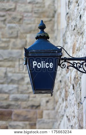 Old fashioned illuminated blue lamp outside a British police station traditionally used since Victorian times