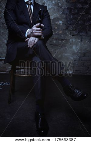 Evil is the new black. Dangerous charming charismatic man pointing a gun at someone while sitting in a chair in a dark room