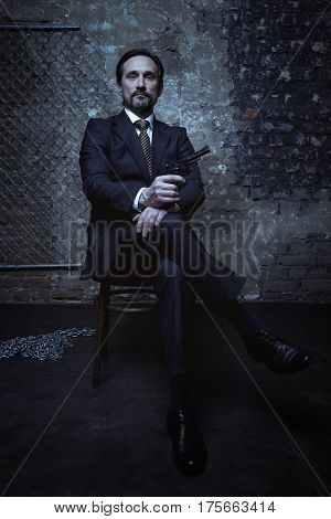 Looking better than anyone. Antagonizing attractive wicked villain wearing an elegant black suit and holding a weapon in his hand while posing for a photographer in a dark room