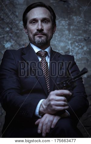 Look of power. Strong charismatic influential gentleman posing for a photographer in a dark studio while sitting in a chair and showing a gun