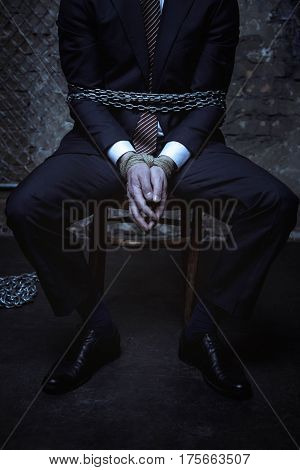 Punishment for dishonesty. Powerful rich classy businessman sitting on a chair loaded with chains while still wearing his business suit
