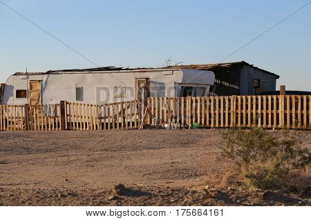 Delapidated mobile home and shed behind fence in rural desert, probablyowned by family of low income, in poverty