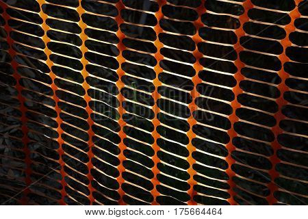 Orange plastic security fence in sunlight against a black background, creating barrier and pattern.