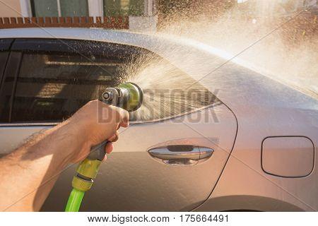 Hand Spraying Water For Car Wash. Private Car Washing. Focus On Spray Gun