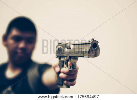 A teenage male holding a gun / Gun violence in school concept