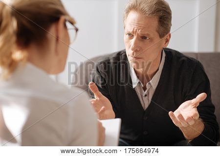 Constant stress. Sad miserable unhappy man looking at his therapist and telling her his story while suffering from stress