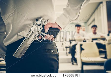 A lecturer holding a gun in his hand in a lecture room / Armed campus concept