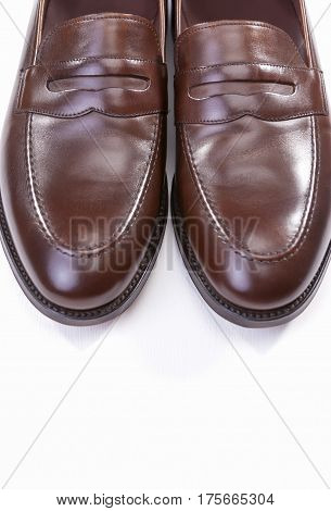 Footwear Concepts. Pair of Stylish Brown Penny Loafer Shoes Against White Background. Placed Together Closely. Vertical Image Orientation