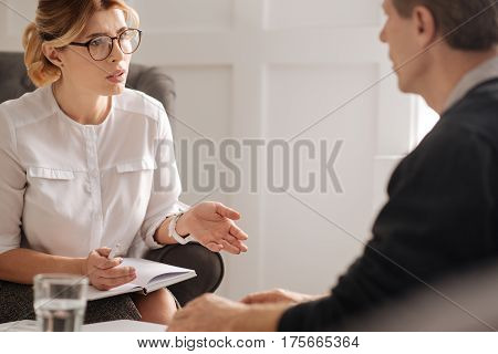 Psychological session. Professional confident intelligent therapist holding a notebook and speaking to her patient while having a psychological session with him