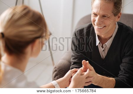 Happy smile. Joyful delighted nice man smiling and looking at his therapist while enjoying his psychological session