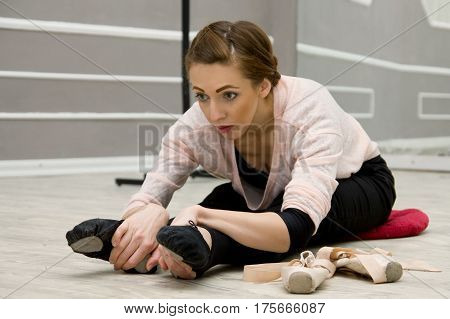 Young Beautiful Graceful Ballerina Resting In Ballet Class Sitting On The Floor, Ballet Shoes, A Pin
