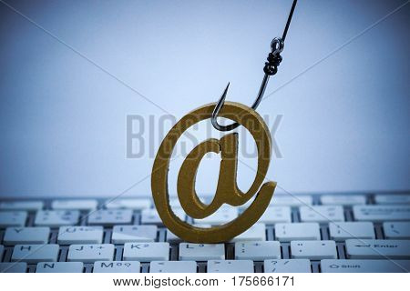 A fish hook with email sign on computer keyboard / Email phishing attack concept
