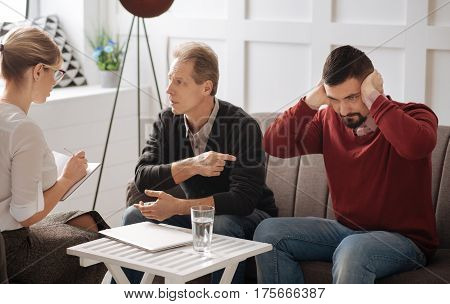 I do not want to hear you. Serious stubborn bearded man sitting on the sofa and pressing his hands to the ears while being unwilling to listen