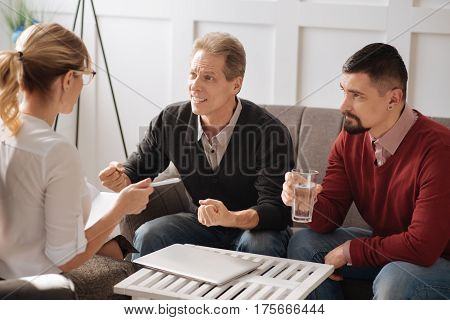Being thirsty. Nice handsome pleasant man holding a glass and drinking water while visiting a psychologist