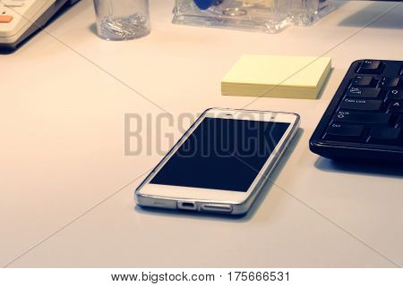mobile phone, keyboard, notebook on table in office; toned photo