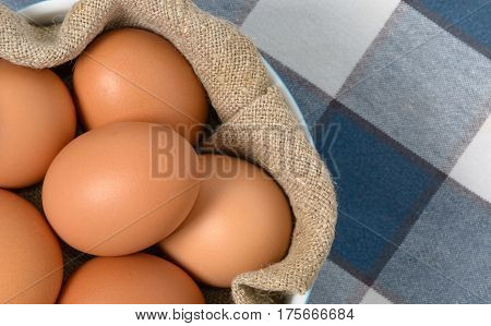 Brown Eggs in bowl with homespun fabric Top view