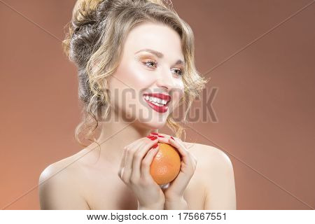 Closeup Portrait of Positive Caucasian Blond Girl with One Orange Fruit in Hand. Posing Against Color Background. Horizontal Image Orientation