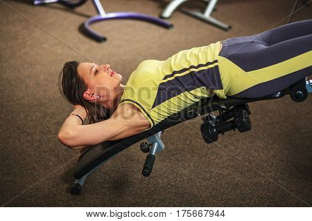 Young Beautiful White Girl In A Yellow And Gray Sports Suit Is Doing Exercises On Training Apparatus