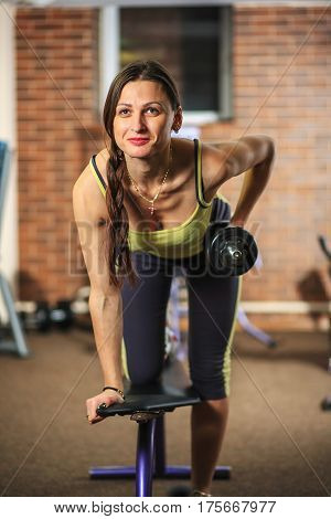 Young Beautiful White Girl In A Yellow And Gray Sports Suit Is Doing Exercises With A Dumbbell On Tr