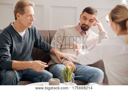 Take a glass of water. Serious thoughtful nice man holding his boyfriends hand and looking at the glass of water while trying to calm him down