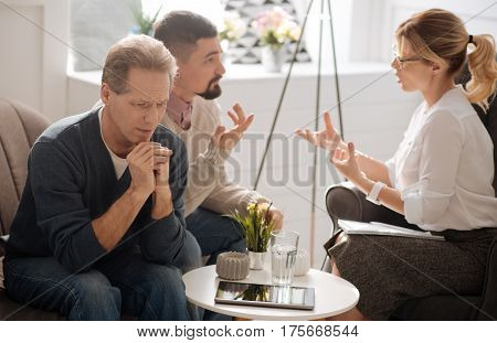 Feeling worried. Depressed miserable unhappy man listening to the conversation and clasping his hands while being worried