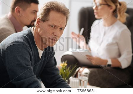 Involved in thoughts. Cheerless thoughtful unhappy man listening to the conversation and thinking about his problems while having a depression