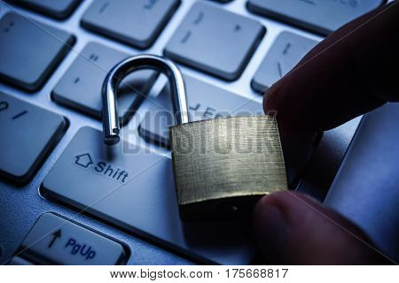 Hand holding unlock security lock on computer keyboard - computer security breach concept