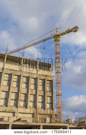 Architecture and Construction Concepts and Ideas. Industrial Construction Site With Mid-Size Crane In Process.HDR Toning.Vertical Image