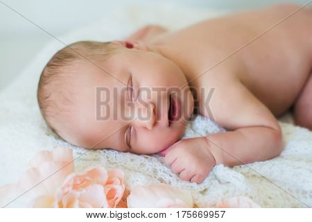 Smiling newborn baby. Head and shoulders shot of a sleeping two week old newborn baby. Light background, sleeping newborn girl