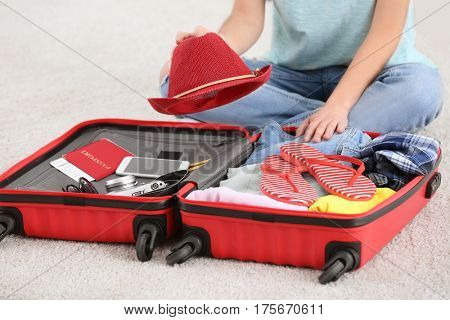 Young woman packing suitcase at home