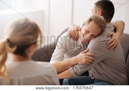 Homosexual relationships. Positive happy delighted gay couple hugging each other and laughing while enjoying their time together