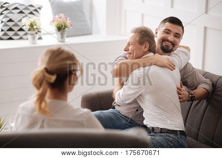 Loving couple. Joyful happy positive gay couple embracing each other and laughing while being in love