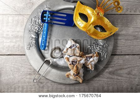 Jewish Pastry Hamantaschen with a mask for Purim Holiday