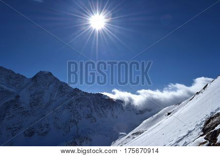 beautiful view of clouds crossing the mountain ridge. awesome mountain landscape with snow-capped peaks, rocks, sky. photo on the theme of winter nature, adventures and travel.