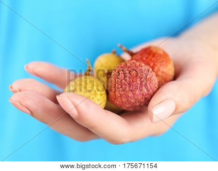 Woman holding heap of longan and litchi