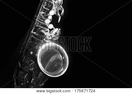 low key alto saxophone and light in the dark background black and white
