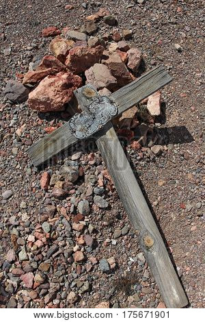 Old weathered wooden cross with metal nameplate toppled on ground in gold mining townsite at  Picacho Landing, Picacho SRA, California