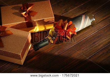 Decorated wine bottle and gift boxes on wooden background