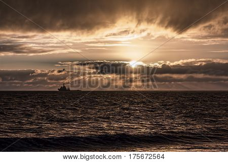 A ship is silhouetted as it sails across the horizon on a calm sea before sunset. A beautiful sepia orange glow as the sun disappears behind drammatic cloud formations.