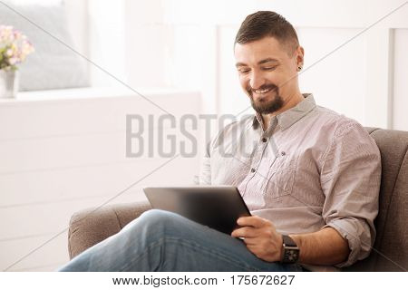 Young entrepreneur. Delighted self employed handsome businessman sitting in his office and using a tablet while working