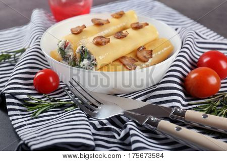 Delicious stuffed cannelloni with mushrooms on plate