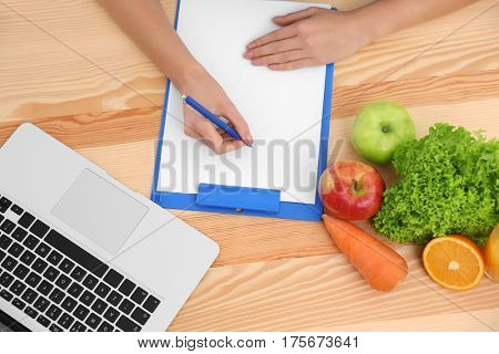 Hands of female nutritionist counting calories in hospital